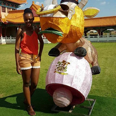 Phindiwe Nkosi next to a Chinese Zodiac ox at Nan Hua Temple in Bronkhorspruit. Photo by SL