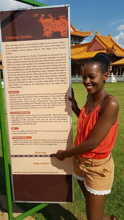 Phindiwe Nkosi next to a Chinese Zodiac sign at Nan Hua Temple in Bronkhorspruit. Photo by SL
